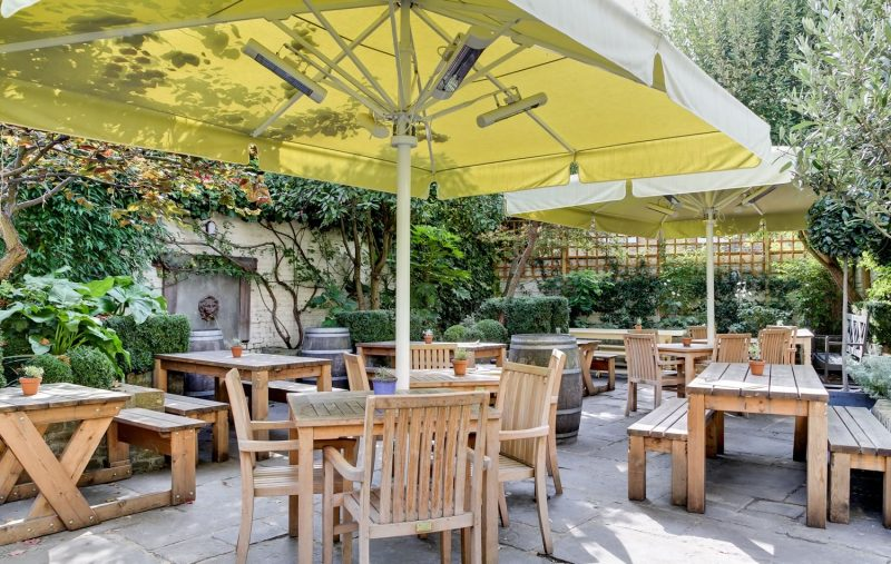 A photo of The Rose beer garden with large parasols and wodden tables